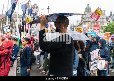 4 juin 2019. Londres, Royaume-Uni. Trump anti rassemblement à Westminster. Un protestataire se cache de la pluie sous la plaque.