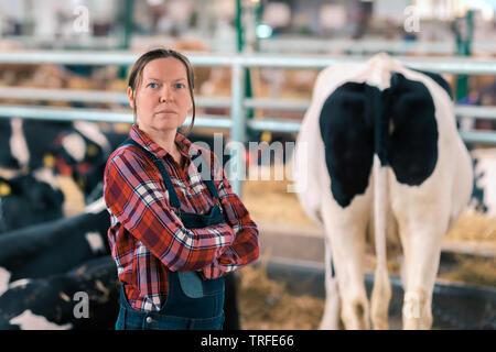 La productrice en enclos sur une ferme d'élevage laitier, portrait de satisfait fier avec son cowgirl du bétail en étable ranch Banque D'Images