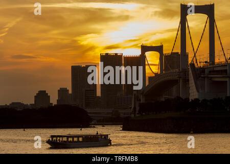 Un yakatabune bateau de plaisance dans la baie de Tokyo au coucher du soleil en face de pont en arc-en-ciel, Odaiba, Tokyo, Japon. Jeudi 30 Mai 2019
