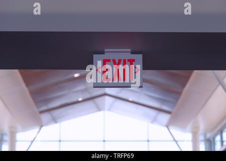 Panneau de sortie. Red Fire Escape signer accrocher sur le plafond dans l'aéroport. Banque D'Images