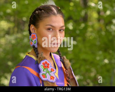 Les jeunes des Premières Nations cries femme porte son costume traditionnel et pose pour la caméra au cours de la Barrie Native Friendship Centre Pow-wow. Banque D'Images