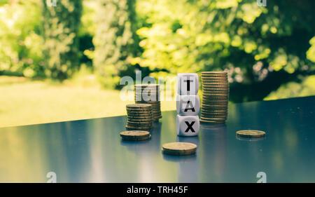 """Formulaire dés le mot """"taxe"""" placé à côté des piles de pièces. Banque D'Images"""