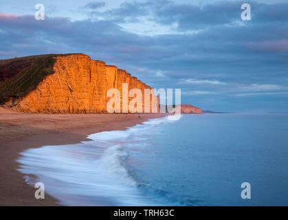 Vagues se brisant sur la plage sous les falaises de l'Est, West Bay, sur la côte jurassique, Dorset, England, UK