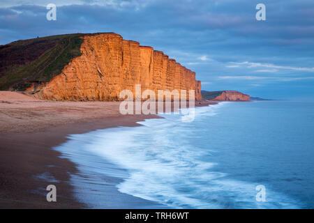 Vagues se brisant sur la plage sous les falaises de l'Est, West Bay, sur la côte jurassique, Dorset, England, UK Banque D'Images