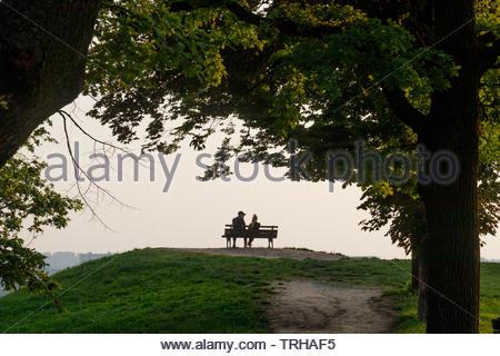 Silhouette d'un couple sur un banc de parc en admirant le coucher du soleil Banque D'Images