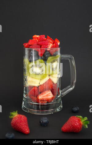 Petits fruits, pomme et kiwi coupé et mis dans le verre contre le fond noir Banque D'Images