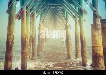 Une vue sous une jetée sur une plage avec une mer agitée et un peu de brouillard que le téléspectateur regarde par piliers à l'océan à l'autre extrémité. Banque D'Images