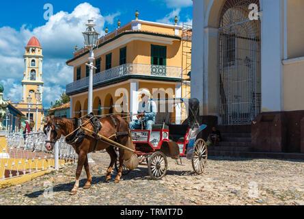 Transport de chevaux en passant par la Plaza Mayor à un tarif sur le clocher de l'église de saint François à l'arrière-plan de Trinidad, Cuba, Caraïbes Banque D'Images