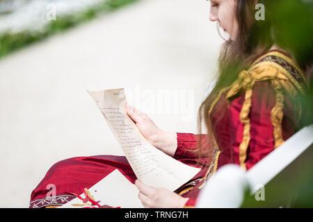 Femme en robe renaissance la lecture d'une lettre. Petite profondeur de champ, l'accent est mis sur la liste Banque D'Images
