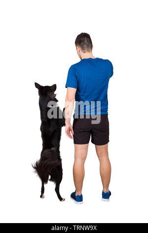 Vue arrière pleine longueur du jeune homme sa formation propriétaire obéissant border collie dog standing on hind paws isolated over white background. Les droits de l'animal et f Banque D'Images