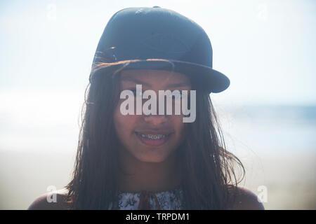Portrait d'une jeune fille asiatique adolescentes portant une casquette de baseball noire à la plage en plein soleil Banque D'Images