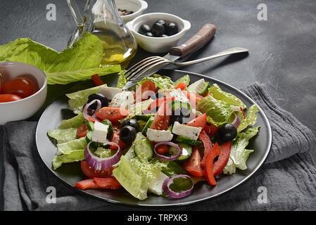Salade grecque avec concombre, tomates cerises, poivrons, laitue, oignon rouge, olives et huile d'olive et le fromage feta. Concept d'aliments sains