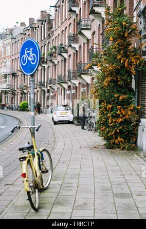 Sac à dos avec l'homme s'arrête sur le trottoir pour regarder son téléphone cellulaire. Près de Lui sont un signe de vélo bleu, un vélo jaune, une petite voiture blanche et orange fleurs