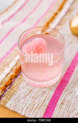 Cocktail pétillant rose faite avec du jus de grenade, de gin, de l'eau tonique et agité avec de la glace et versé sur un jus d'orange sanguine ice cube en forme de coeur