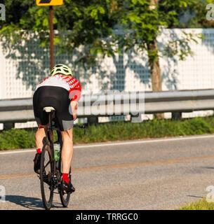 Un cycliste se débarrasser de l'appareil photo de la formation sur les routes sur un matin d'été ensoleillé. Banque D'Images