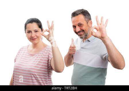 Cheerful couple thumb up comme geste avec les doigts et bien isolé sur fond blanc studio Banque D'Images