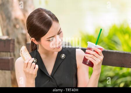 Fille à la question sur le sentiment du goût de pourriture ou de sucre et la nutrition dans son verre de jus de glace Banque D'Images