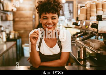 Jeune femme en tablier, debout au comptoir de café. Confident female barista debout derrière comptoir. Banque D'Images