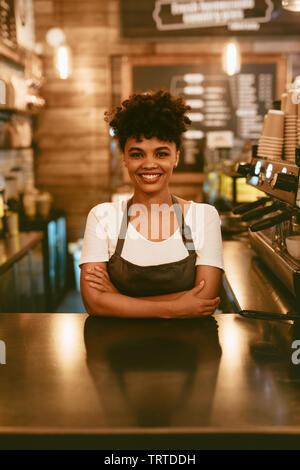 Smiling african woman en tablier, debout au comptoir de café. Confident female barista debout derrière comptoir. Banque D'Images