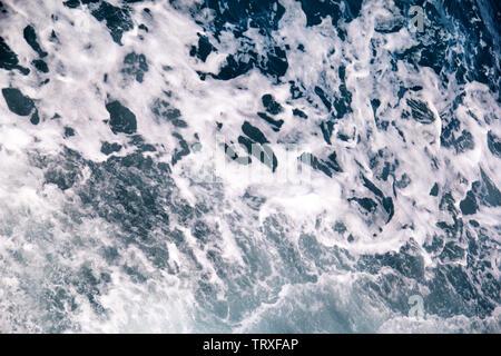 Faites par la turbulence de l'eau de mer de mousse d'un yacht à grande vitesse sur la surface de la mer. Les vagues de la mer bleue avec beaucoup d'écume de mer. Surface de mer avec les vagues. Banque D'Images