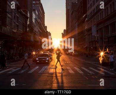 Le soleil brille sur une femme traversant l'intersection avec une longue ombre jetée sur les rues de Manhattan à New York City NYC Banque D'Images