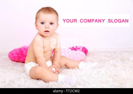 Cute little boy avec oreillers rose sur la moquette dans la chambre Banque D'Images