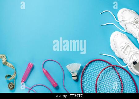 Les équipements de sport. Volant et raquette de badminton, la corde à sauter, les espadrilles et ruban à mesurer sur fond bleu. Sport, remise en forme et d'un style de vie sain Banque D'Images