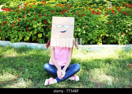 Femme avec boîte en carton sur la tête avec le visage, à l'extérieur Banque D'Images