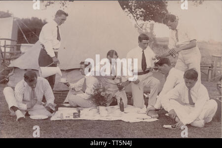 Vintage Début xxe siècle Carte postale photographique de Smartly Dressed Men faire un pique-nique en face de la tente (camping). Banque D'Images
