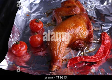 Cuisse de poulet fumé avec des tomates cerises sur l'aluminium close up Banque D'Images