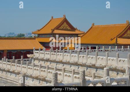 Rangées de piliers en marbre blanc orné en premier plan, en face de l'orange vif toits de bâtiments chinois traditionnels contre le ciel bleu Banque D'Images