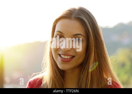 Close-up portrait of belle jeune femme adulte dans la lumière du soleil au coucher du soleil. Jolie jeune fille souriante. Belle femme jouit d'ambiance chaleureuse et la lumière du soleil.