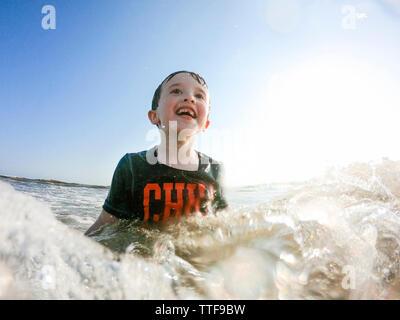 Happy boy piscine en mer contre ciel lors de journée ensoleillée Banque D'Images
