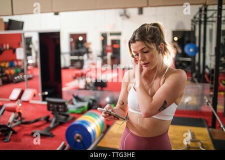 Jeune femme à l'écoute de la musique avec vos écouteurs et smartphone at gym