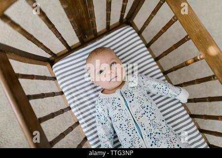 Vue de dessus de la pose bébé dans un berceau en bois