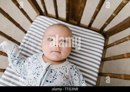 Pose bébé dans un berceau en bois Banque D'Images
