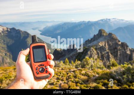 Randonneur utilise le GPS appareil pour naviguer jusqu'à vélo, pic de Douglas, en Colombie-Britannique. Banque D'Images