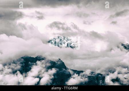 Low angle view of mountains contre ciel nuageux Pendant temps de brouillard