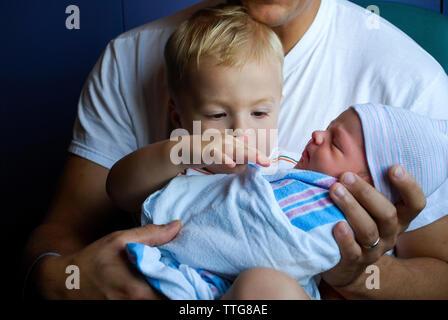 Toucher tout-petit frère nouveau-né enveloppé dans une couverture en cours par le père Banque D'Images