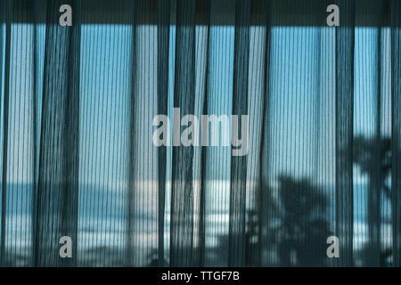 Rideau filet tracé à travers de la fenêtre de chambre d'hôtel donnant sur l'océan Banque D'Images