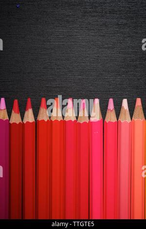 Crayons alignés sur un tableau noir. Banque D'Images