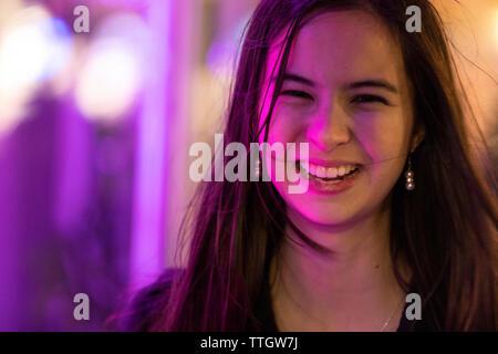 Happy smiling young woman portrait multiracial dans les lumières de la ville.