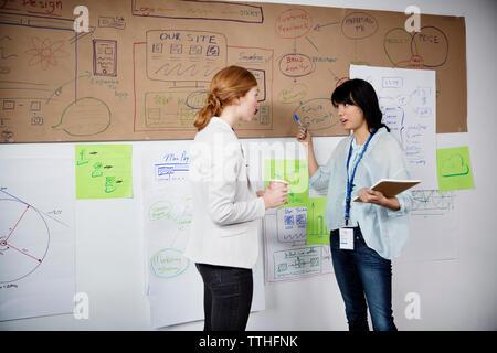 Plus de Businesswomen discussing charts alors que standing in office