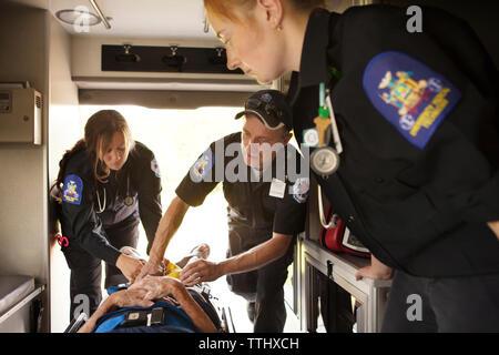 L'équipe de sauvetage d'offrir un traitement au patient en ambulance Banque D'Images