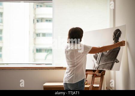 Vue arrière du woman painting on easel à art studio Banque D'Images