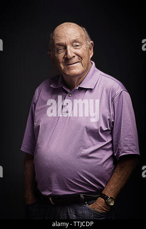 Portrait of senior man with hands in pockets debout sur fond noir Banque D'Images