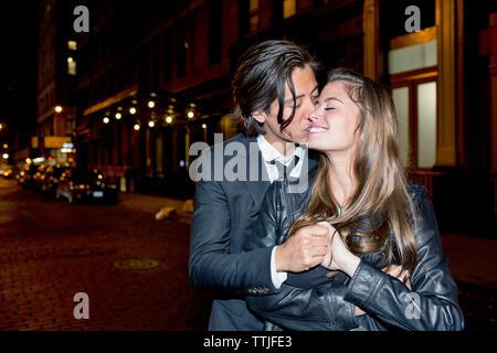 Couple romantique petite amie en se tenant sur le city street at night Banque D'Images