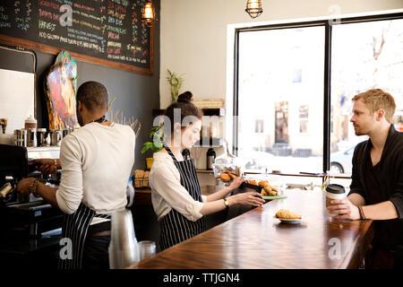 Femme à l'aide d'ordinateur de bureau tout en servant la clientèle à muffins Banque D'Images