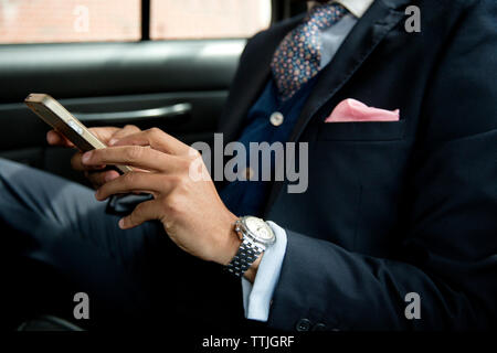 Portrait of businessman using mobile phone while sitting in car