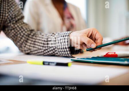 Portrait de main tenant un crayon alors que working in office Banque D'Images